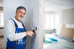 Älterer Mann, der an dem elektrischen Einbau arbeitet stockfoto