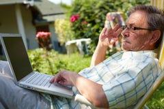 Älterer Mann, der den Computer im Freien verwendet Stockfotos