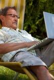 Älterer Mann, der den Laptop im Freien verwendet Stockfotografie
