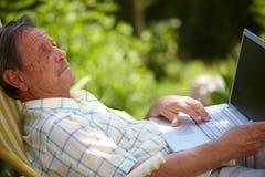 Älterer Mann, der den Laptop im Freien verwendet Stockfotos