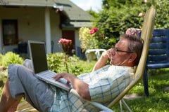 Älterer Mann, der den Laptop im Freien verwendet Stockfoto