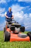 Älterer Mann, der den Rasen mäht. Lizenzfreie Stockfotos