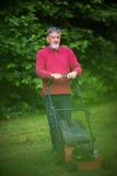 Älterer Mann, der den Rasen mäht Stockfotos