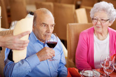 Älterer Mann, der den Wein im Restaurant schmeckt Lizenzfreie Stockfotografie