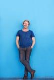 Älterer Mann, der an der blauen Wand und am Lächeln lehnend steht Stockfoto