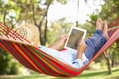 Älterer Mann, der in der Hängematte mit E-Buch sich entspannt Stockfotografie