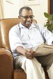 Älterer Mann, der in der Lehnsessel-Lesezeitung sitzt Lizenzfreies Stockbild