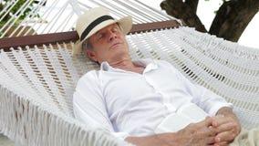 Älterer Mann, der in der Strand-Hängematte sich entspannt stock video