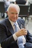 Älterer Mann, der die Ansicht mit Alkoholglas betrachtet Stockfotos
