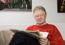 Älterer Mann, der die Papiere liest Stockfoto