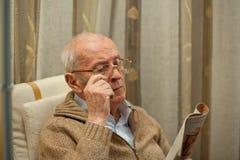Älterer Mann, der die Zeitung liest Stockbild