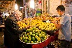 Älterer Mann, der die Zitronen und andere saftige Früchte auf dem asiatischen Straßenmarkt kauft Lizenzfreies Stockbild