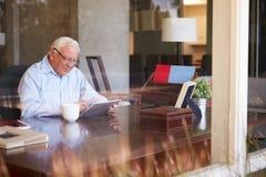 Älterer Mann, der Digital-Tablet durch Fenster verwendet Stockbild