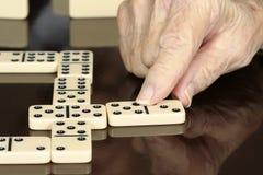 Älterer Mann, der Dominos spielt Lizenzfreies Stockfoto
