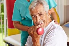 Älterer Mann, der Dumbbelltraining tut Stockfoto