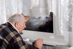 Älterer Mann, der durch ein Fenster nachts blickt Stockfotografie