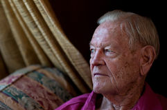 Älterer Mann, der durch Fenster im Haus sitzt Stockfoto