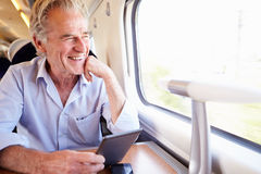 Älterer Mann, der e-Buch auf Zug-Reise liest stockfotografie