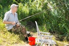 Älterer Mann, der ein entspannendes Tagesfischen aufwendet Lizenzfreie Stockbilder