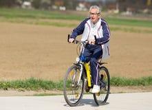 Älterer Mann, der ein Fahrrad reitet Stockbild