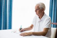 Älterer Mann, der ein Farbtonbuch verwendet Stockfoto