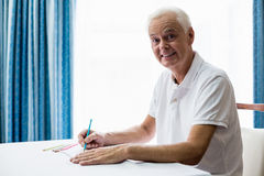 Älterer Mann, der ein Farbtonbuch verwendet Lizenzfreie Stockfotografie