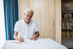 Älterer Mann, der ein Farbtonbuch verwendet Lizenzfreie Stockfotos