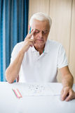 Älterer Mann, der ein Farbtonbuch verwendet Lizenzfreies Stockbild
