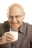 Älterer Mann, der ein Glas Milch trinkt stockbilder