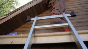 Älterer Mann, der ein Haus durch die Stellung auf Baugerüst baut stock video