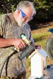 Älterer Mann, der ein Vogel-Haus aufbaut Stockfoto