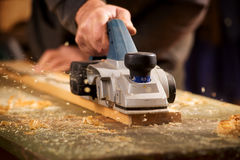 Älterer Mann, der eine Planke des Holzes planiert lizenzfreies stockfoto