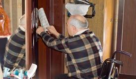 Älterer Mann, der eine Zeitung durch eine Tür zurückholt Lizenzfreies Stockbild