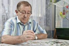Älterer Mann, der an einem Puzzlespiel arbeitet lizenzfreie stockfotos