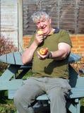Älterer Mann, der einen Apfel anbietet. Lizenzfreie Stockbilder