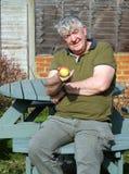 Älterer Mann, der einen Apfel anbietet. Stockfotos