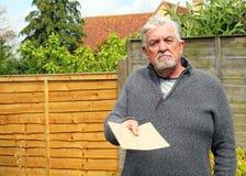 Älterer Mann, der einen einfachen braunen Umschlag gibt Stockbilder