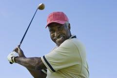 Älterer Mann, der einen Golfclub schwingt Lizenzfreies Stockbild