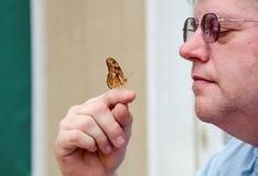 Älterer Mann, der einen Schmetterling hält lizenzfreie stockfotos