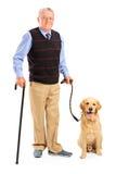 Älterer Mann, der einen Stock und einen Hund anhält Lizenzfreie Stockbilder