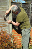 Älterer Mann, der einen Zaun repariert. Stockfotos