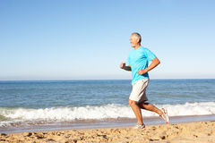 Älterer Mann, der entlang Strand läuft Stockfoto