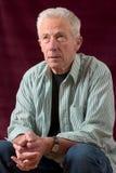 Älterer Mann, der in entspannter Haltung sitzt Stockfotos