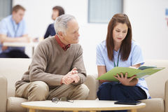 Älterer Mann, der Ergebnisse mit Krankenschwester bespricht Stockbild