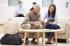 Älterer Mann, der Ergebnisse mit Krankenschwester On Digital Tablet bespricht Stockfotografie