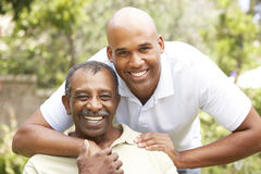 Älterer Mann, der erwachsenen Sohn umarmt stockbild