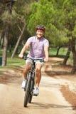 Älterer Mann, der Fahrradfahrt im Park genießt Stockfotos