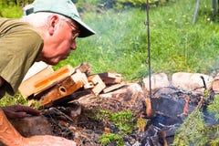 Älterer Mann, der Feuer bildet Stockfotos