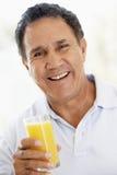Älterer Mann, der frischen Orangensaft trinkt Stockfotos