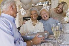 Älterer Mann, der Geschenk von den Freunden empfängt Stockbild
